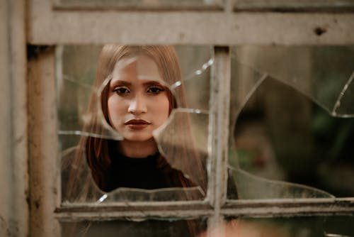Calm young woman looking at camera through broken window