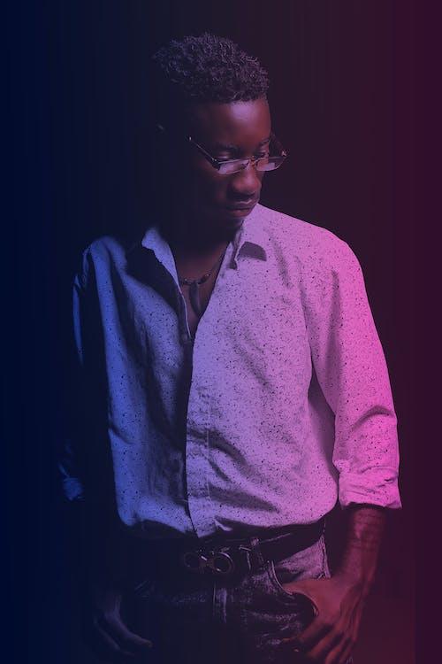 Thoughtful stylish black man in dark room with neon illumination