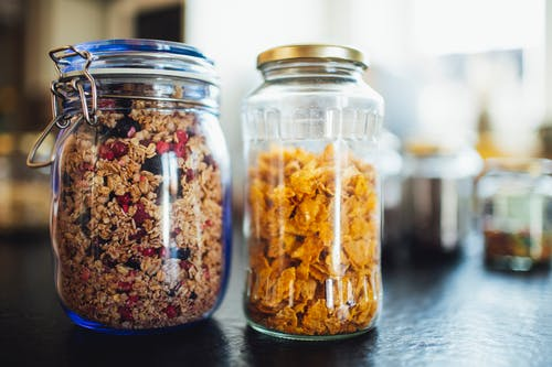 Glass jars with healthy cornflakes and muesli placed  on table in kitchen