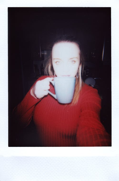 Woman in Red Sweater Drinking from White Ceramic Mug