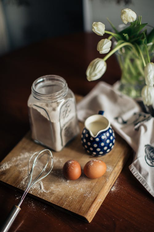 From above of vase with white flowers placed near fresh milk eggs and glass jar with flour on cutting woody board at kitchen