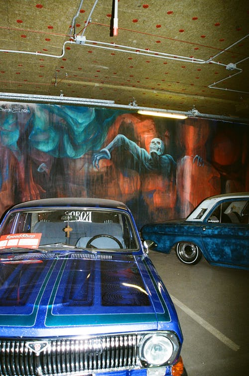 Vintage Cars at a Parking Lot With Graffiti on the Walls