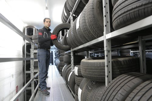 Man in Black Jacket Standing Beside Black Tires