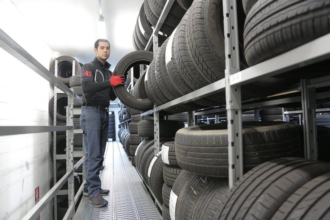Man in Black Jacket Standing Beside Black Tires