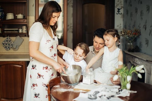 Foto De Mujer Horneando Cerca De Su Familia