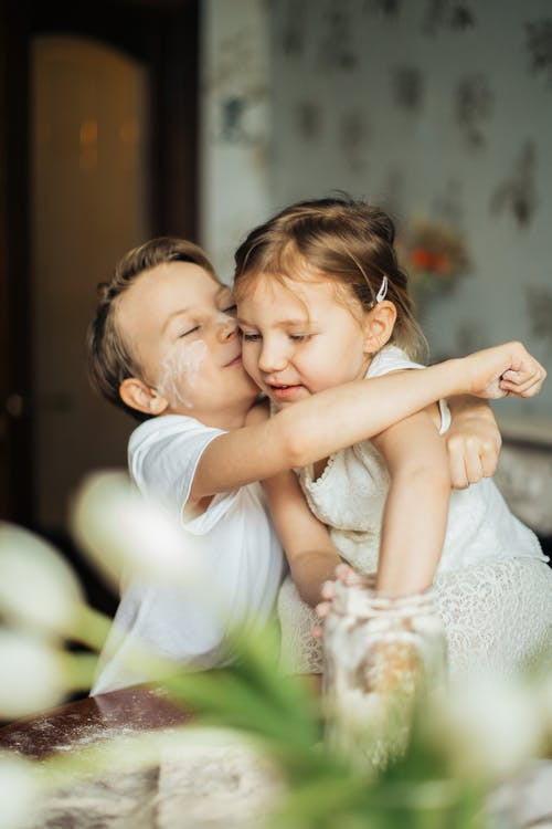 Photo of Boy Hugging His Sister