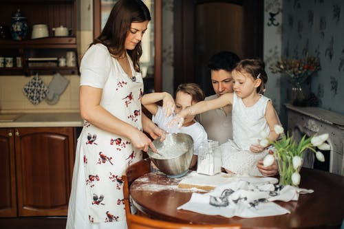 Photo of Woman Baking Near Her Family