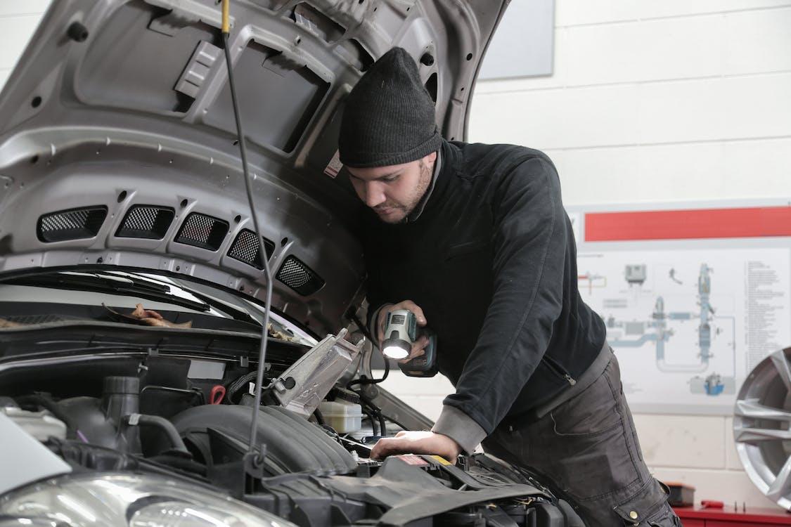 Mann In Schwarzer Jacke Und Schwarzer Strickmütze, Die Den Automotor Inspiziert
