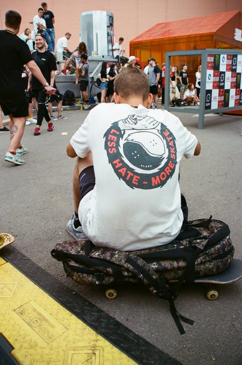 Person Sitting on a Backpack and a Skateboard