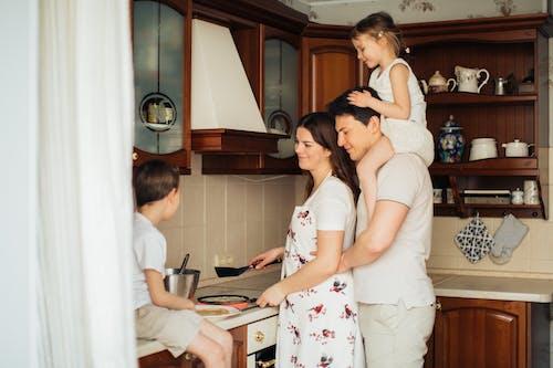 Foto De Mujer Cocinando Cerca De Su Familia