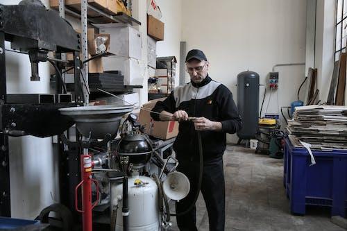 Focused mechanic repairing compressor hose in workshop