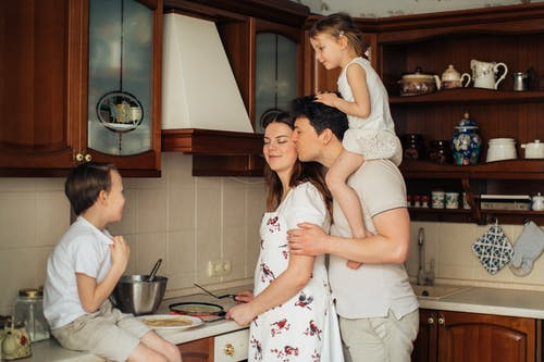 Photo of Man Kissing His Wife While Cooking