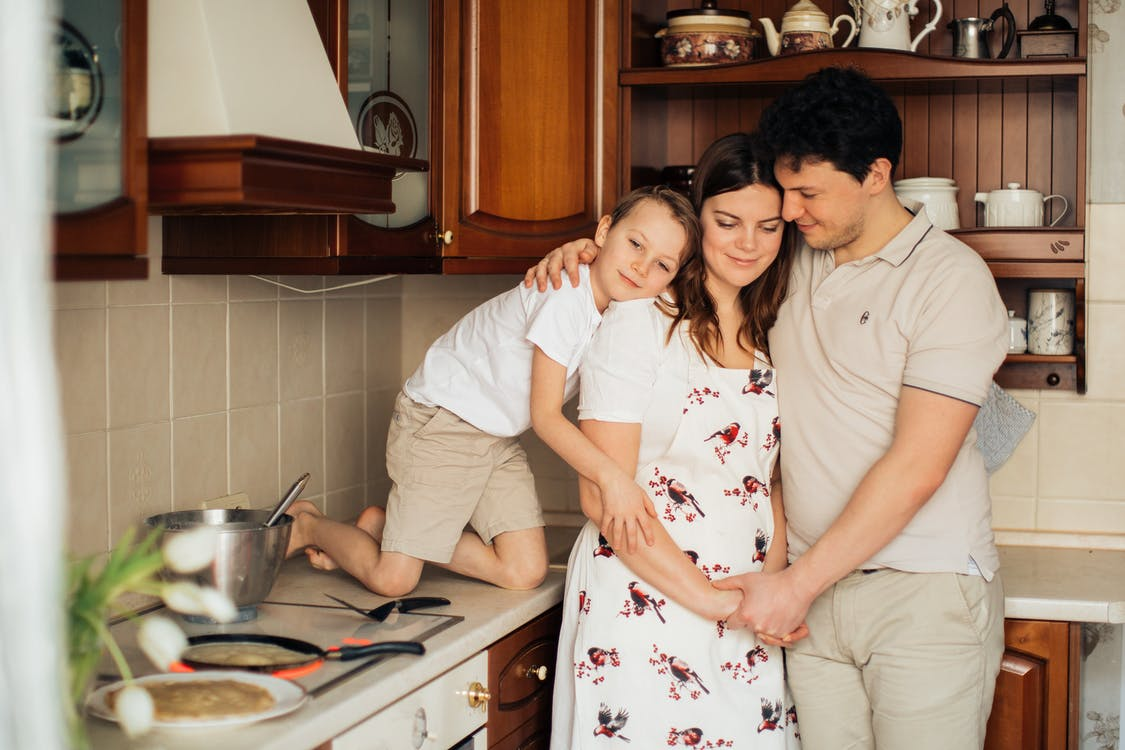 Photo of Family Standing Near Kitchen Counter While Smiling