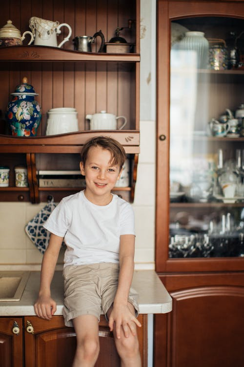 Photo of Boy Sitting on Kitchen Counter While Smiling