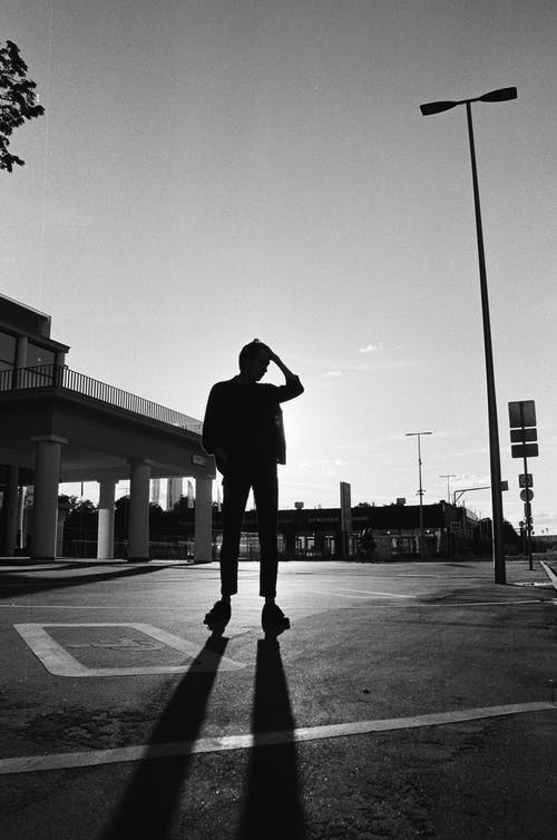 Silhouette of a Man Standing on a Parking Lot