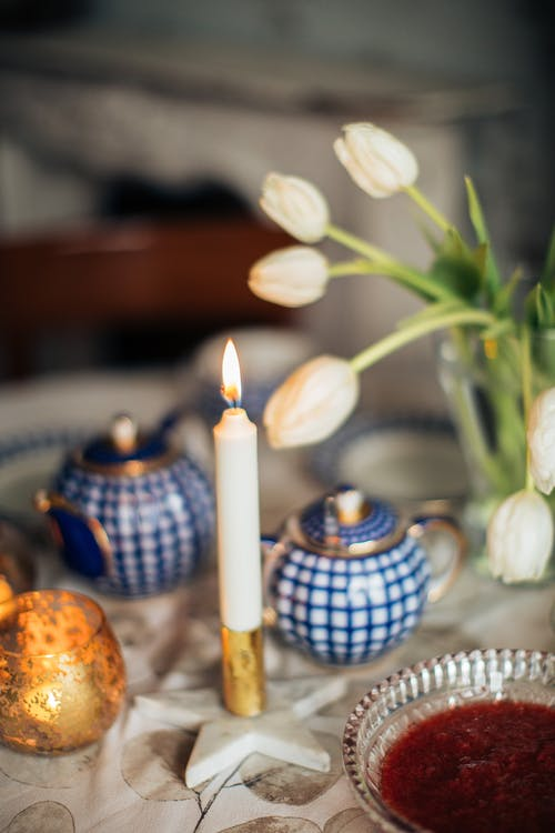Candle burning near flowers and tableware