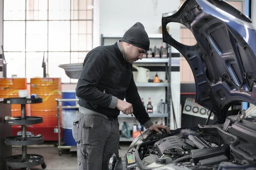 Photo of Man Inspecting Car Engine