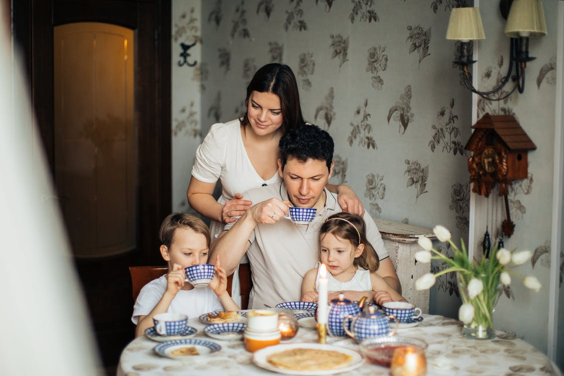 Contented family drinking tea with crepes together while sitting at table with candles at cozy kitchen with cuckoo clock on wall