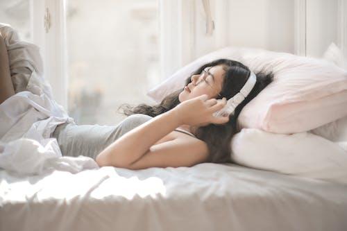 Женщина, лежа на кровати, слушая музыку