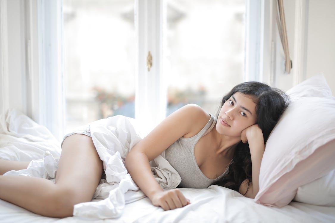 Vrouw In Grijze Tanktop Liggend Op Bed
