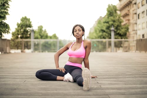 Woman in Pink Sports Bra and Black Leggings Sitting on Wooden Floor