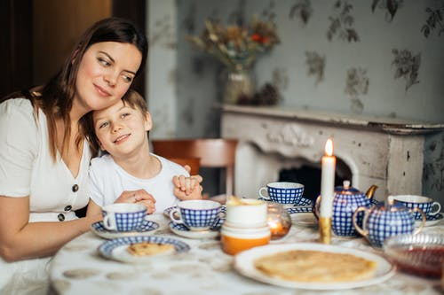Happy mother and son having breakfast at home