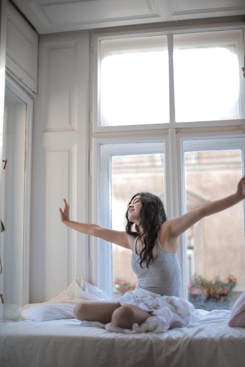 ベッドに座っている間灰色のタンクトップの女性の写真