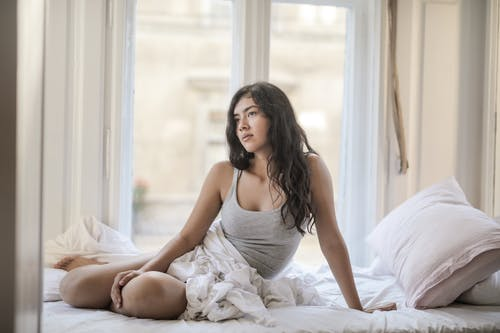 Woman in Gray Tank Top Sitting on Bed