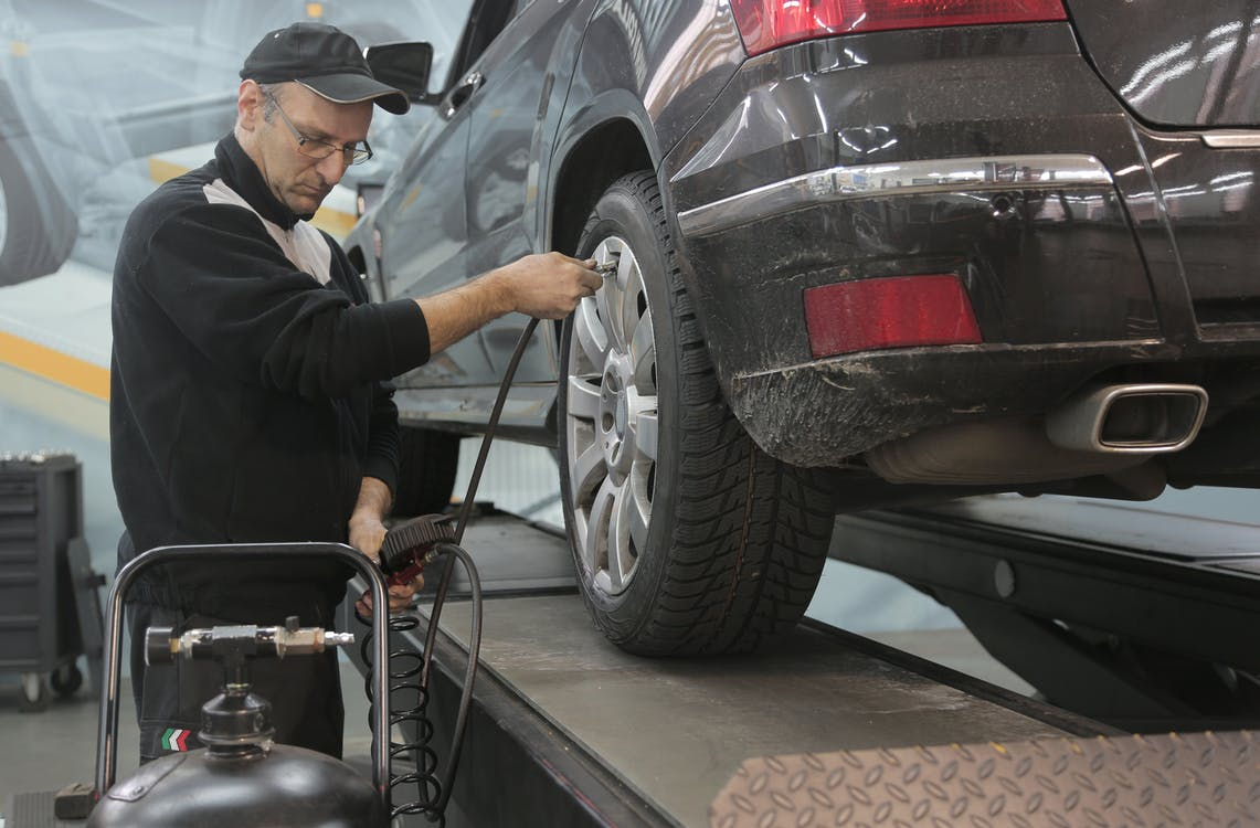 Serious car mechanic pumping up car wheel in modern service garage