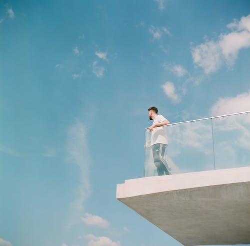 Man in White Long Sleeve Shirt and Joggers Standing on Balcony