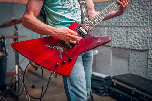 Crop male musician in tee shirt and jeans standing and playing red electric guitar with drums behind