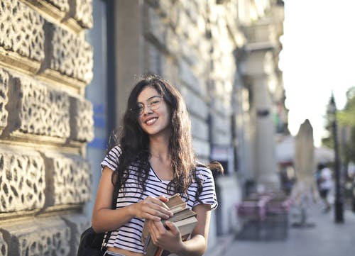 Woman in Black and White Stripe Shirt Holding Books