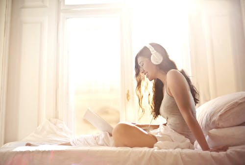 Young happy female with earphones using laptop while sitting on bed in soft daylight by window at cozy bedroom