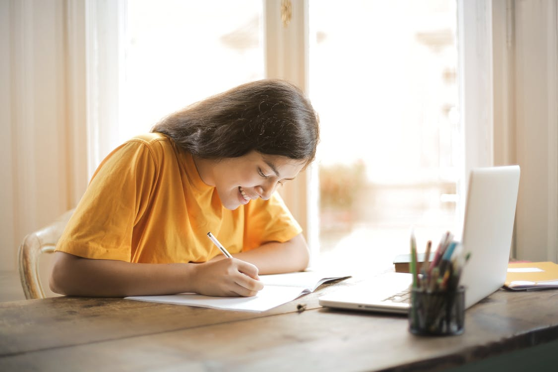 Woman in Yellow Shirt Writing on White Paper