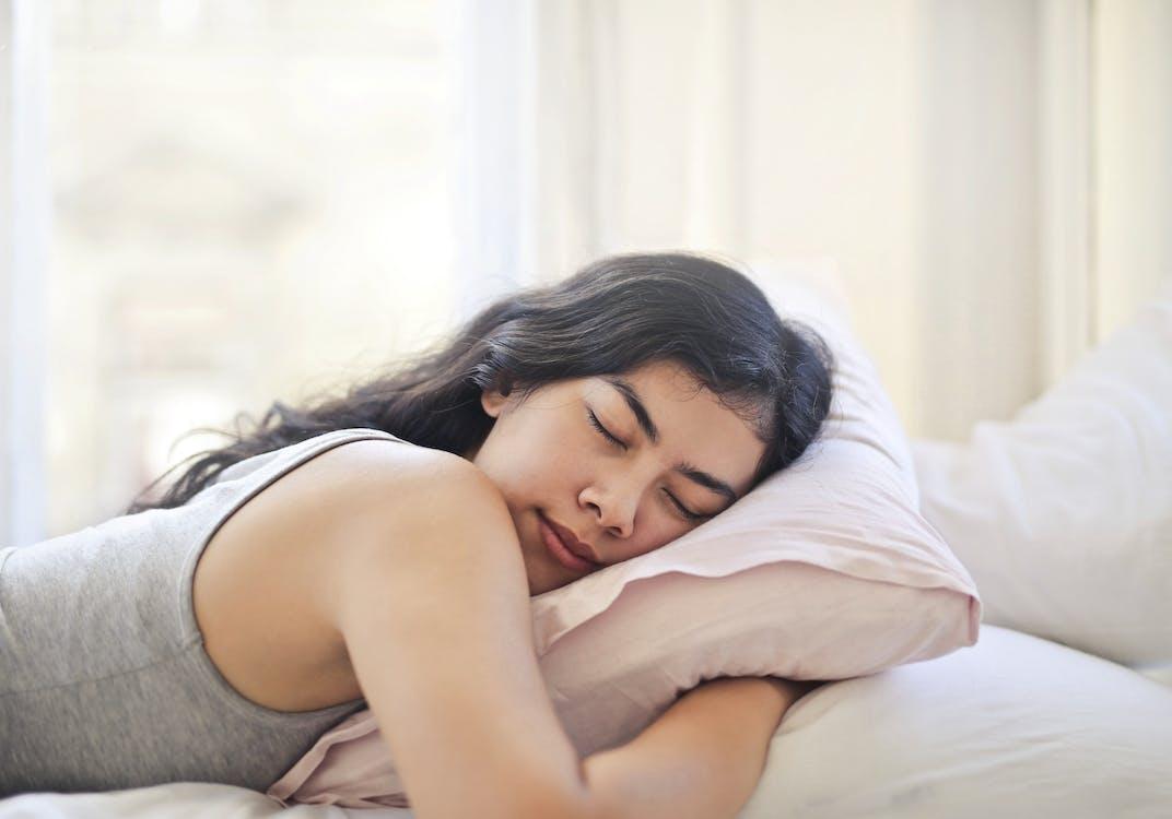 Женщина в серой майке, лежа на кровати