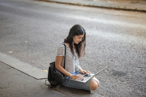 Woman in Black and White Striped Shirt Sitting on Sidewalk Using Macbook Pro