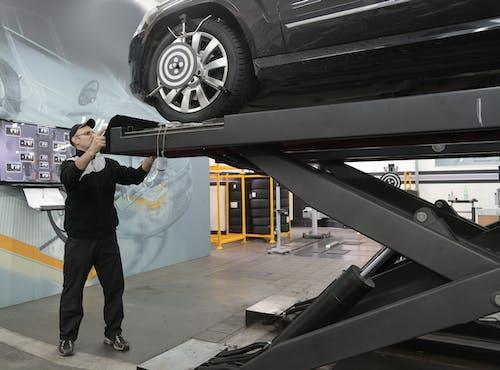 Serious mechanic checking car wheels on lift in modern car service garage