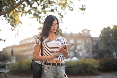 Woman in Black and White Striped Shirt and Blue Denim Jeans Holding Tablet