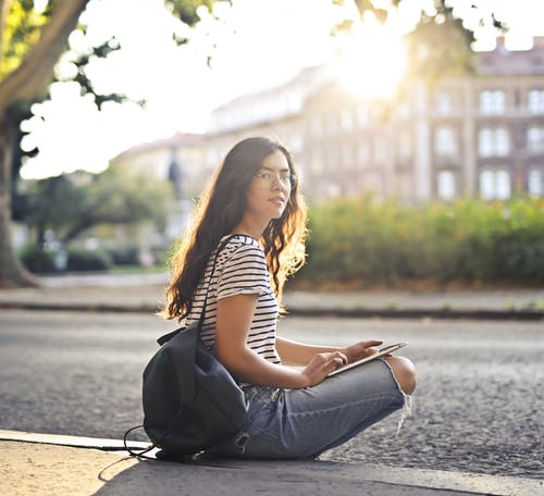 Woman in Black and White Striped Shirt and Blue Denim Jeans Sitting on Sidewalk