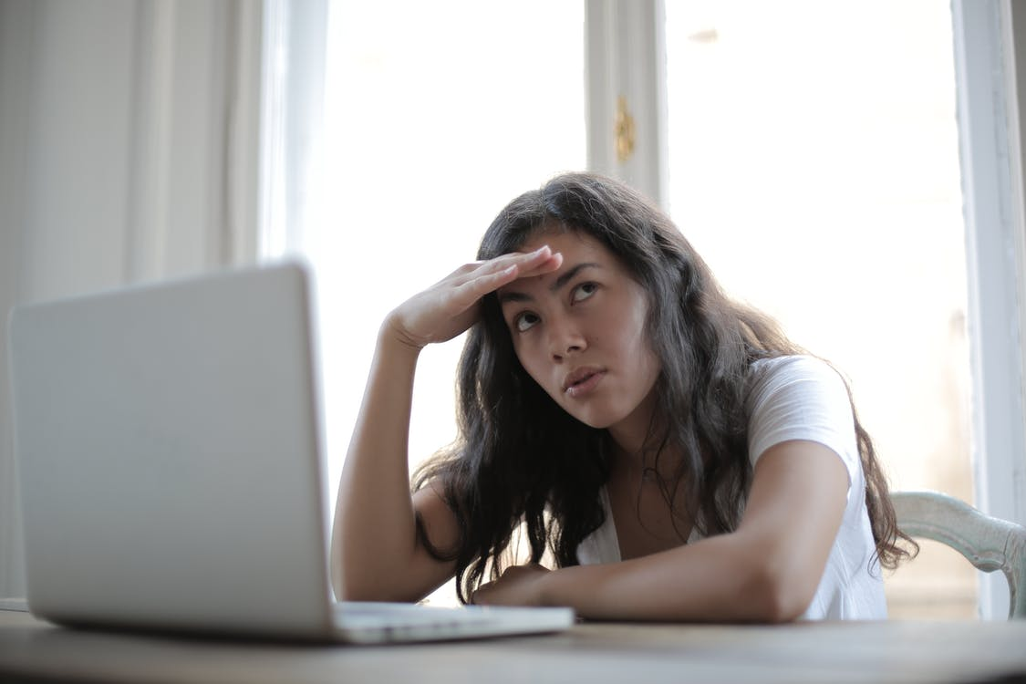 Irritated ethnic female entrepreneur in casual wear sitting at table with netbook and touching head while waiting for internet connection during remote work