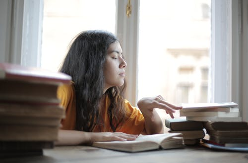 Smart female student reading books at home