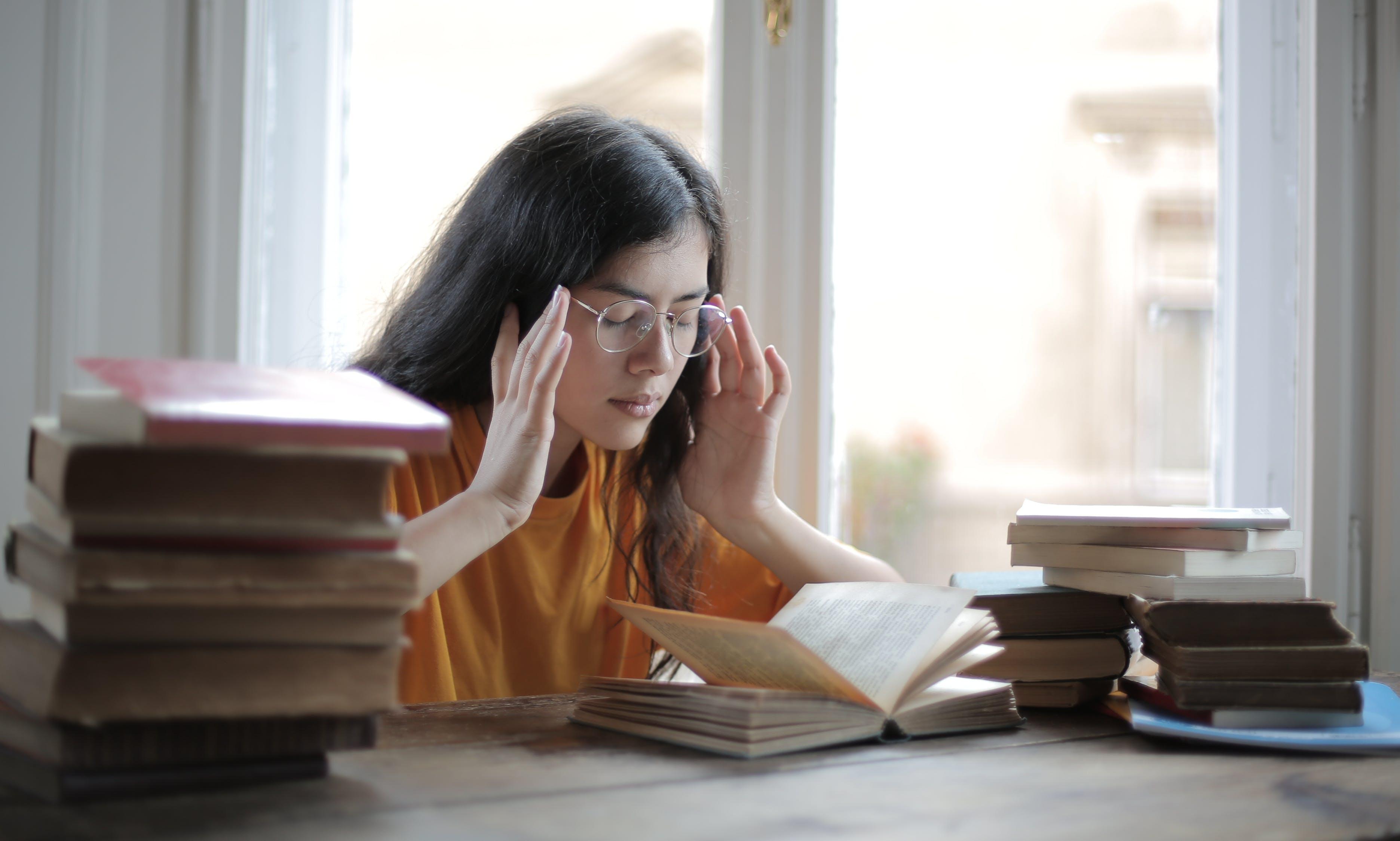 図書館で頭痛に苦しんでいる女子学生