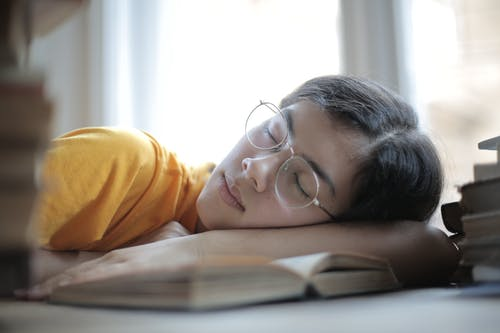 Exhausted female student sleeping at table in library