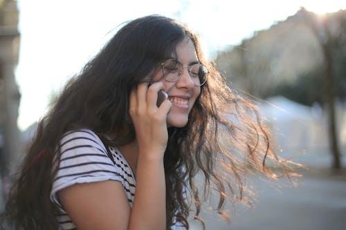 Positive woman speaking on smartphone on street
