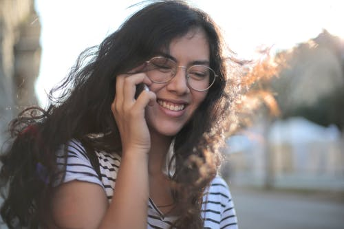 Cheerful young woman making phone call on street