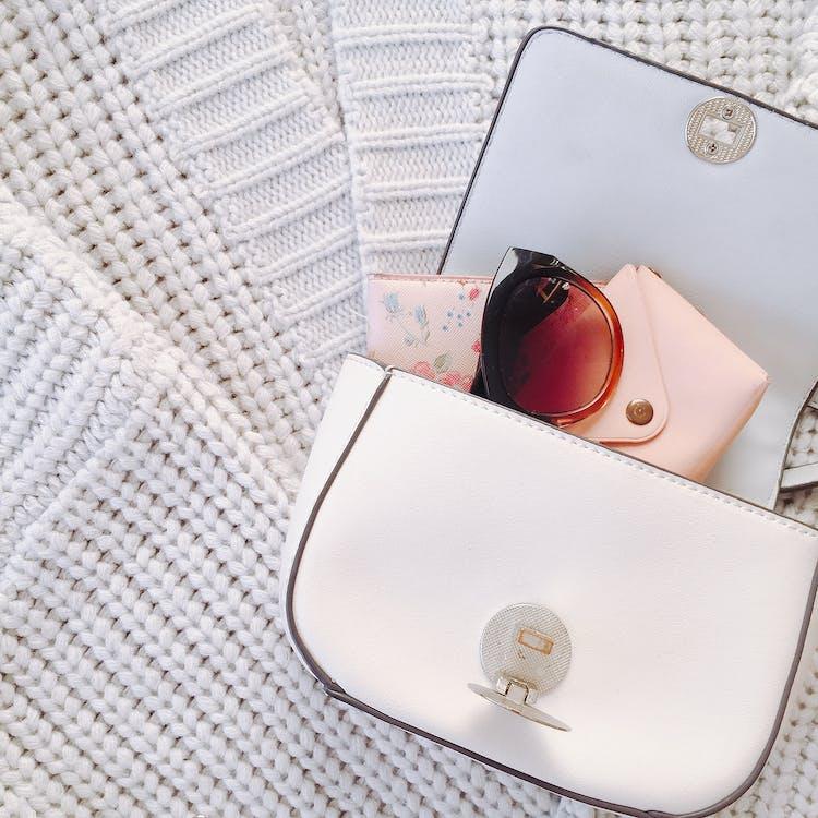 Trendy handbag with sunglasses on knitwear