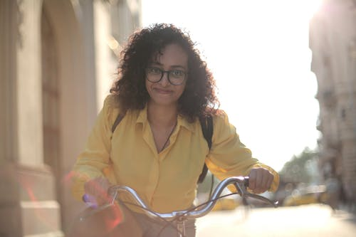 From below cheerful young curly woman in glasses with backpack smiling at camera while riding bicycle along street in sunny day