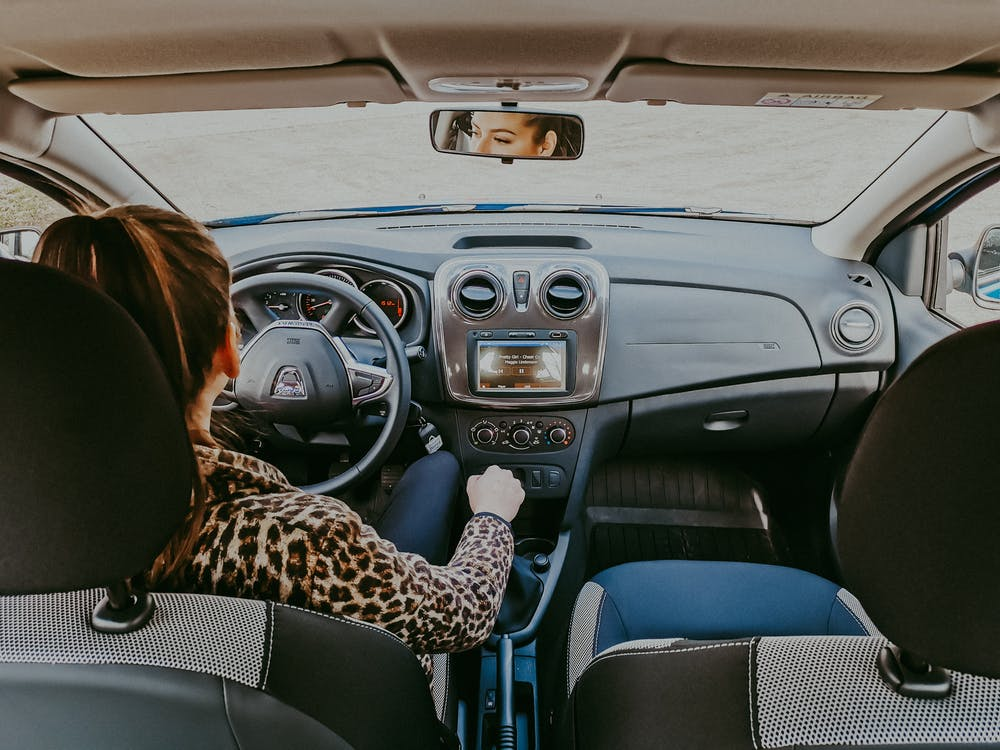 Woman driving modern car along