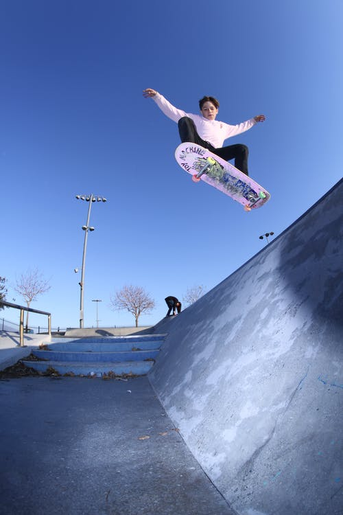 From below of modern teen doing flip trick on skateboard jumping high above ramp in park