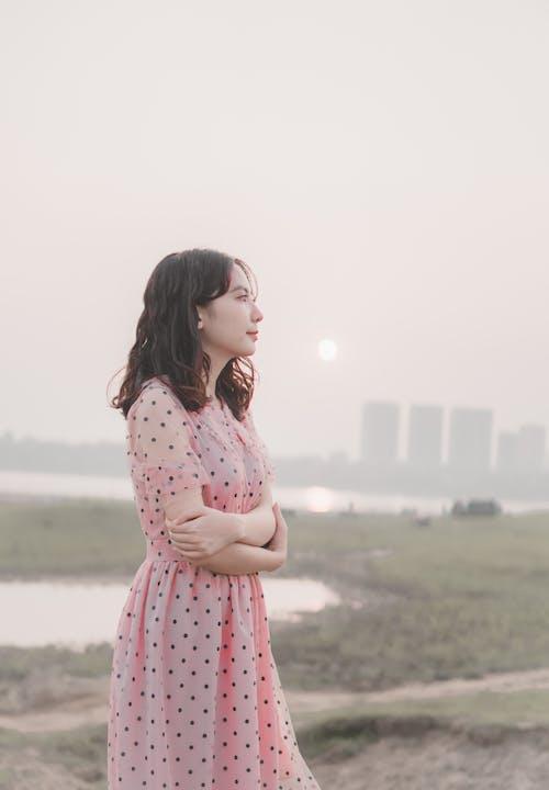 Dreamy Asian woman on lawn near river at sundown